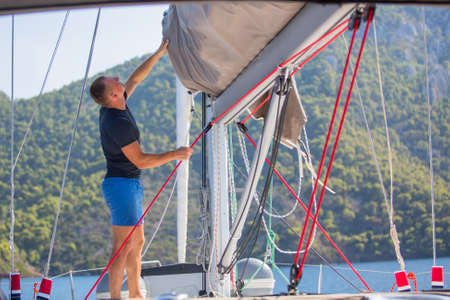 yachtsman: Yachtsman pulls the rope controlling the sail on sailing boat.