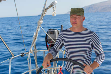 Young man skipper at the helm sail boat, controls ship during sea yacht race. Luxery vacations, sailing, adventure, travel. Stock Photo