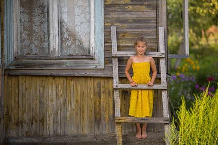 modelos posando: Una niña cerca de la casa de pueblo.