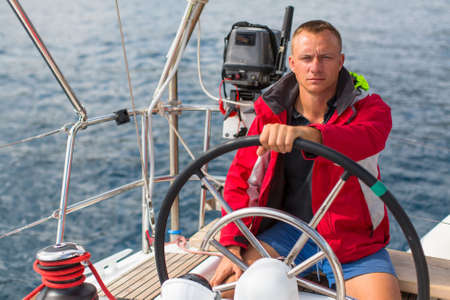Skipper at the helm controls of a sailing yacht. Lifestyle, sport and leisure. Stock Photo