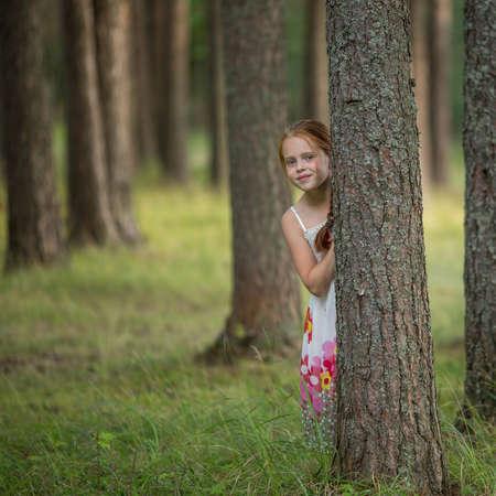 Cute little girl peeking from behind a tree in a pine forest. 免版税图像