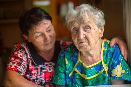 mamma: Sad elderly woman, in background hugging adult daughter.