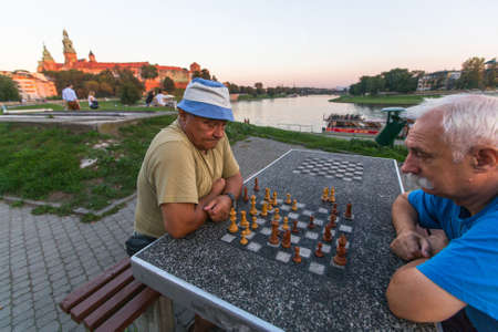 dozens: KRAKOW, POLAND - FEB 8, 2016: Unidentified elderly mens play chess on the embankment of Vistula. There are about 40 parks in Krakow including dozens of gardens and forests.