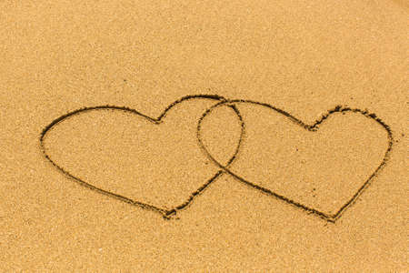 evoking: Two entangled hearts drawn out on a sandy beach.