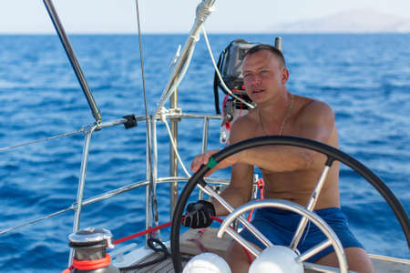 route master: Man captain at the helm controls of a sailing boat during sea yacht race. Stock Photo