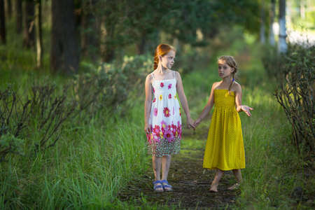 Two kids girls talking in the Park holding hands.