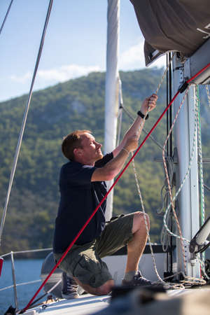 yachtsman: Yachtsman pulls the rope on the mast, on his sailing yaht boat on the sea. Stock Photo