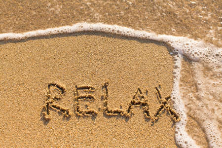 evoking: Relax - drawn on the sand of a sea beach.