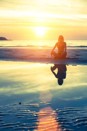 Female silhouette with reflection in water, meditation pose at sunset.