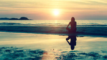 Silhouette of young girl in yoga pose sitting on the beach during amazing sunset. Stock Photo