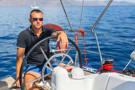 route master: Captain at the helm controls of a sailing boat during sea yacht race.