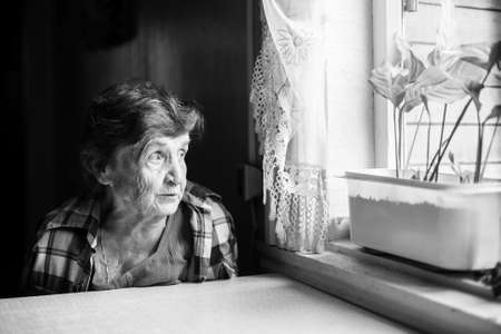 sadly: An elderly woman sadly looking out the window. Black-and-white photo.