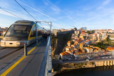 reaches: PORTO, PORTUGAL - JAN 11, 2017: Train of Porto Metro on Dom Luis iron Bridge in Old Town. The network has 6 lines and reaches seven municipalities within the metropolitan Porto area.