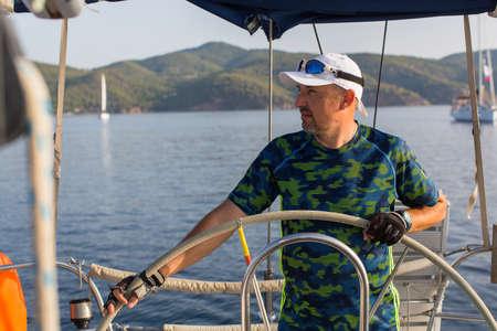 steers: Man skipper steers sailing boat on the Sea. Luxury yacht.