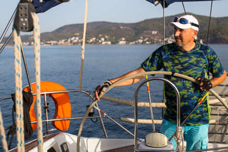 operates: A man stands at the helm and operates the sailing vessel.