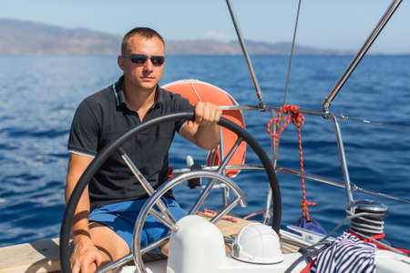 steers: Man skipper steers boat sailing yacht on the Sea.