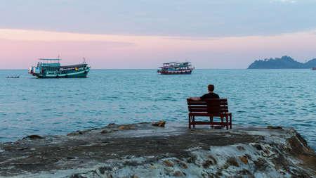 Hombre solo en la orilla noche del mar.