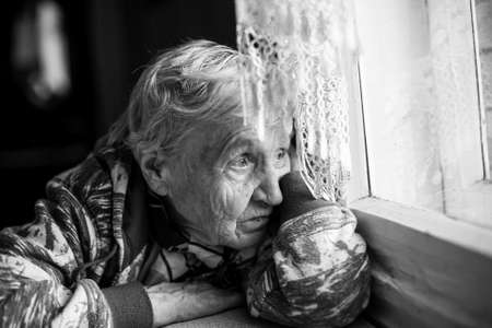 Granny older woman sadly looking out the window. Black-and-white photo.