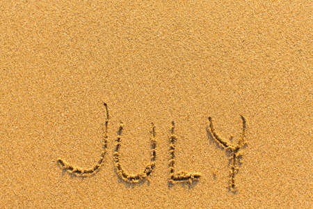 JULY drawn by hand on a golden sandy sea beach.