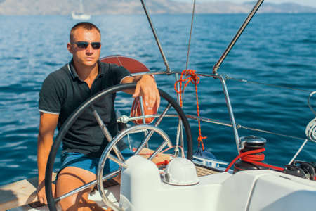 helm: Man on his sailing yacht boat. Stock Photo