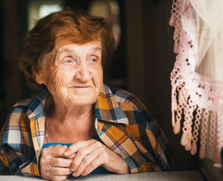 An elderly woman is looking out the window.