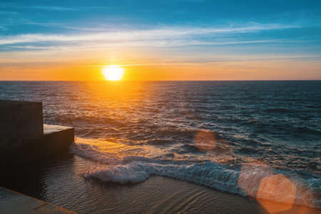 Wonderful sunset at the sea pier, flare and rays. Stock Photo