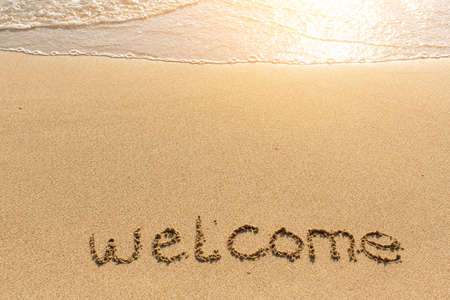 welcome word drawn on the sand beach with the soft wave stock
