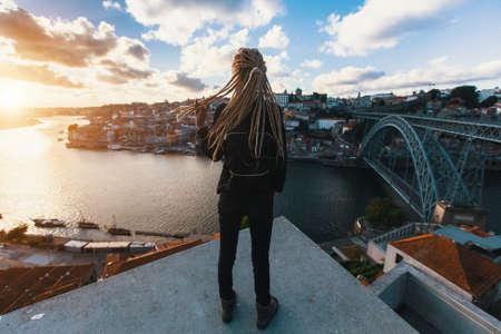 Girl with blonde dreadlocks standing on the background of the bridge Dom Luis I over Douro river, Porto, Portugal. Stock Photo
