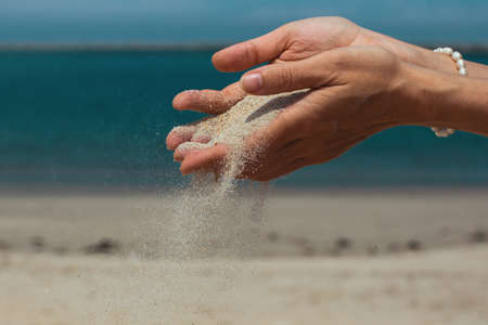 Sand pours through fingers against the sea.
