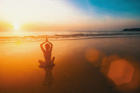 Yoga silhouette of woman in Lotus pose at sunset beach. photo
