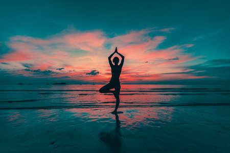 Yoga woman silhouette on sea coast at amazing sunset. photo