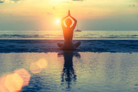 Silhouette woman practicing yoga at seashore during sunset. Health, meditation and tranquility. photo