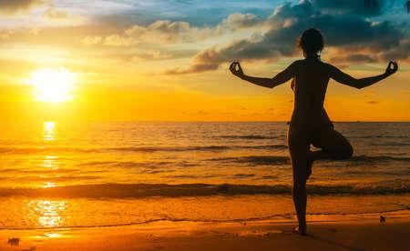 Silhouette yoga woman on sea coast at sunset. photo