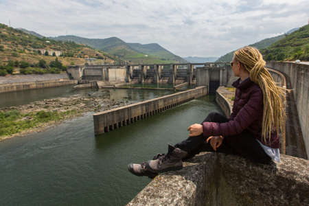 Young woman sitting near an old hydroelectric plant Stock Photo