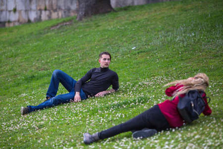 sexes: Young guy posing for a female photographer lying in the meadow.