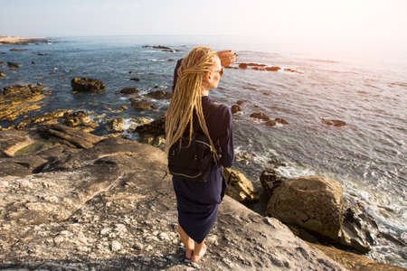 rastas: Young woman with blonde dreadlocks standing on the rocky shore of the ocean toward the sun. View from the back. Foto de archivo