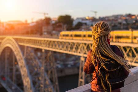 rastas: Joven mujer con dreadlocks (desde la parte posterior) cumple la puesta de sol en la plataforma de observación frente al puente de Dom Luis I a través del río Duero en Oporto, Portugal.