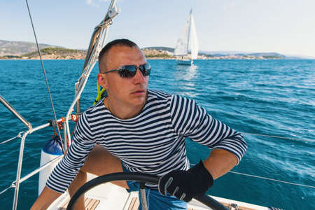 Skipper at the helm on the sailing boat. Ship controls during sea yacht regatta. Stock Photo