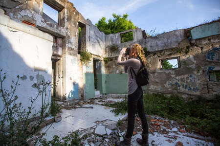 Young woman taking pictures of ruins abandoned buildings.