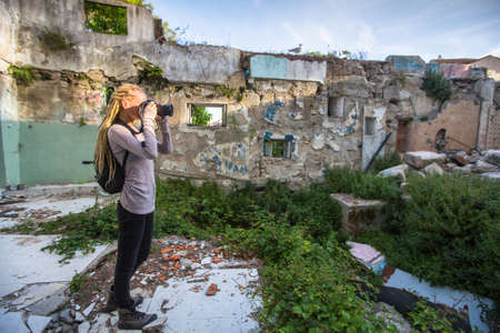 warehouse building: Young woman taking pictures of ruins abandoned buildings.