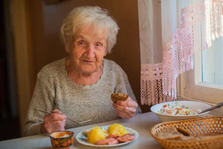 An elderly woman eats sitting at the table. Foto de archivo
