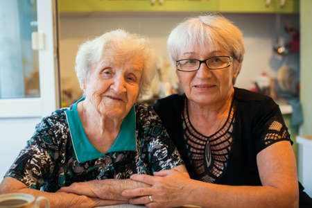 An elderly woman with her adult daughter. photo