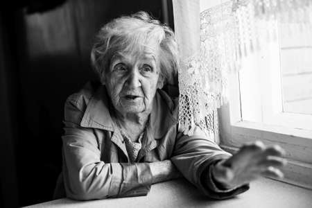 Elderly woman gesturing with hands while sitting at the table. Black and white photography. photo