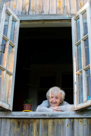 Elderly woman, a grandmother, looks from window of a village house. photo