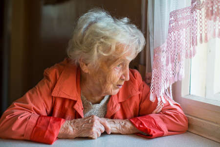 An elderly woman looks out the window of the house. photo
