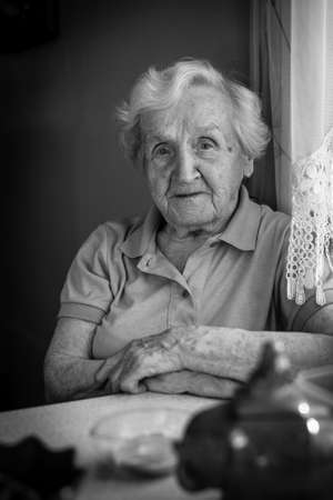 Monochrome portrait of elderly woman sitting at the table. photo