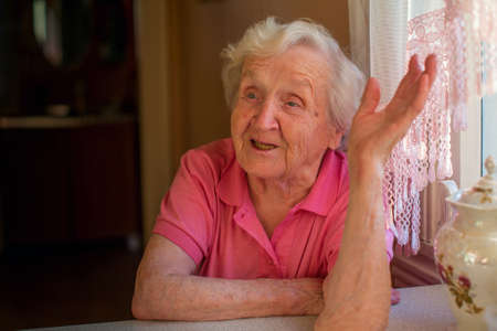 Elderly woman in red talking animatedly sitting at the table. photo