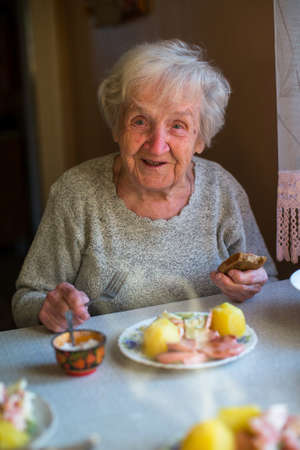 An elderly woman dines at home. photo