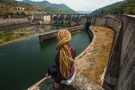 stalker: Young woman with dreadlocks sitting near the old power plant. Stalker. Stock Photo