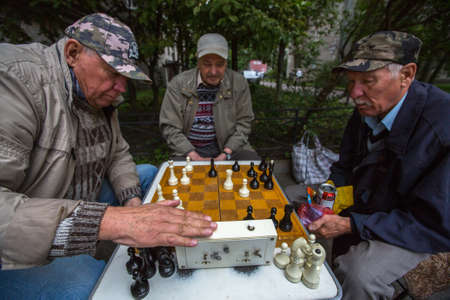 St. PETERSBURG, RUSSIA - SEP 2, 2017: Pensioners play chess in the courtyard of an apartment building. In Petersburg among the population the share of pensioners is approximately 24.4 percent. Editorial